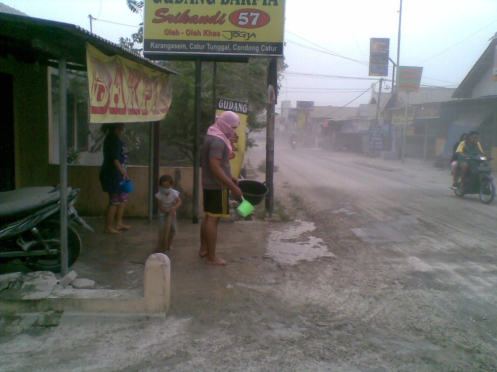 warga membersihkan debu vulkanik